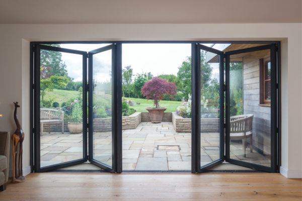 black bi-folding doors opening up into the garden of a home