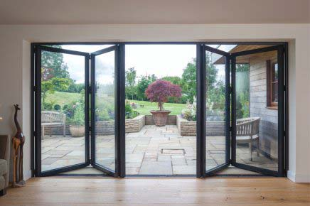 black bi folding doors opening out into the garden of a home