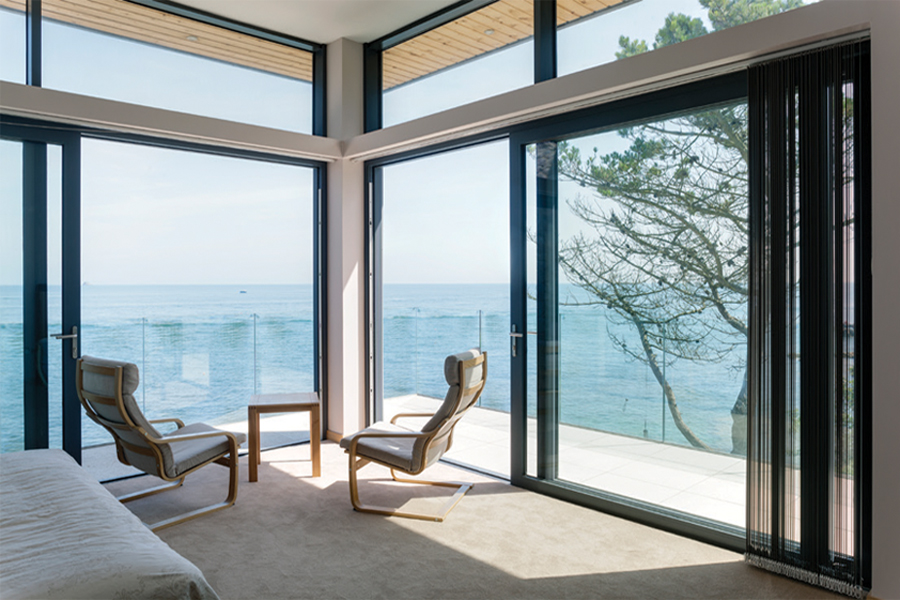 black patio sliding doors opening onto a balcony on a sea front home