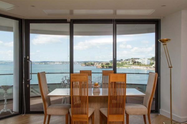 black aluminium patio sliding doors providing stunning views of coastal line from dining room