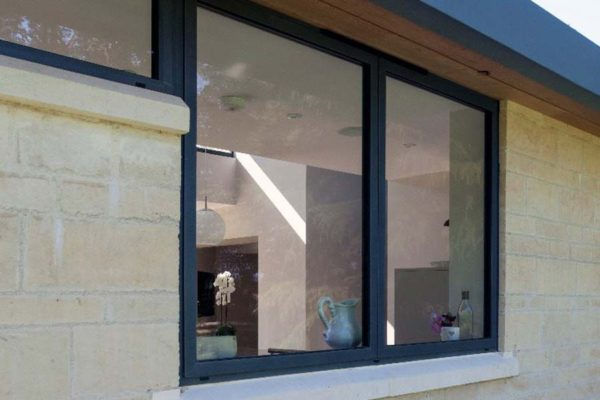 application shot of a grey aluminium casement window on the outside of a house