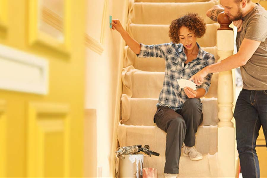 couple decorating their home deciding on paint with colour swatches