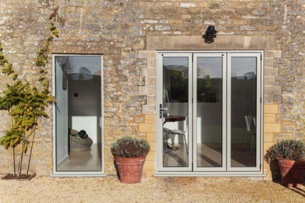 slimline light grey bi-folding doors shot from the outside of a home