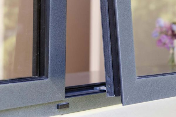 close up of grey aluminium casement windows opening from the outside