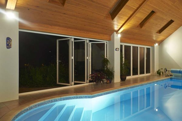 smarts visofold 1000 doors opening up a swimming pool area into a garden at night time